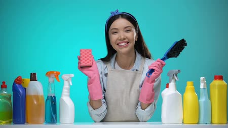 disinfectant : Smiling housewife with brush and sponge looking at camera, detergents on table Stock Footage
