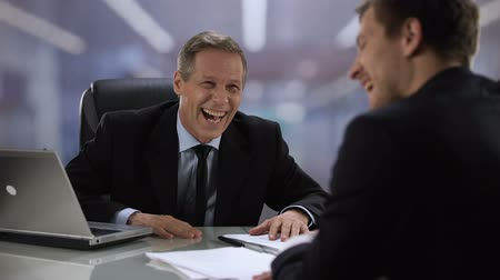 vaga : Friendly company boss and male worker laughing, giving high five at meeting