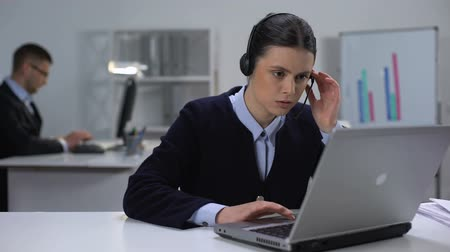 yardım hattı : Call center manager in headset checking data on laptop, customer support Stok Video