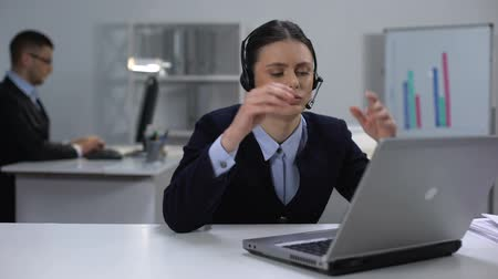телефон доверия : Tired call center operator taking off headset and closing laptop, workday end