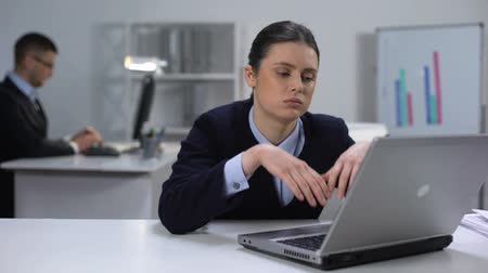 számvitel : Bored female manager texting on laptop, procrastination issue, avoiding work