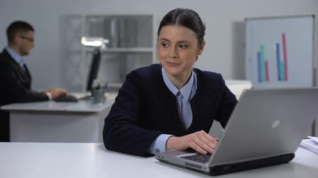 ethic : Cute female manager working on laptop, looking at male colleague, secret love Stock Footage