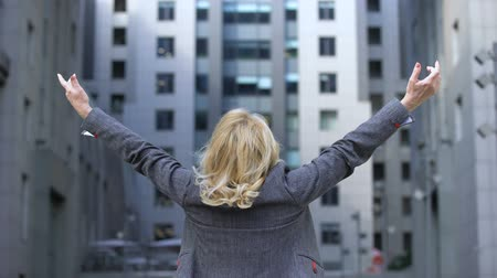optimistický : Carefree blond woman in formal suit raising hands up back view, female wellness Dostupné videozáznamy