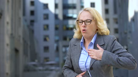 dalgın : Aged female manager feeling sudden chest pain talking on phone, nervousness Stok Video