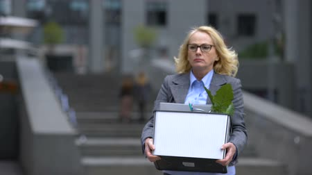 licenziamento : Aged woman with stuff box leaving office building, pension age, work opportunity
