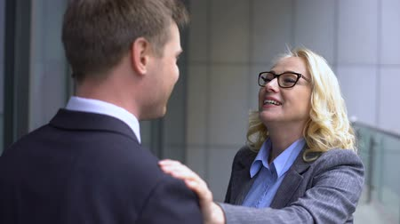 internar : Aged female manager praising young company trainee, satisfied with work result Stock Footage