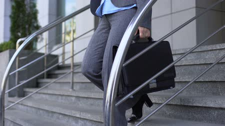 dismissal : Sad aged woman in suit sitting office building stairs, senior age unemployment Stock Footage