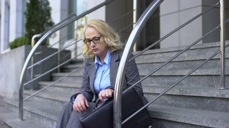 dismissal : Depressed company manager thinking of work dismissal sitting outside office