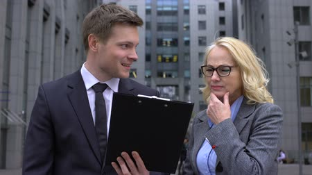 criticize : Senior business lady criticizing business project offered young male colleague Stock Footage