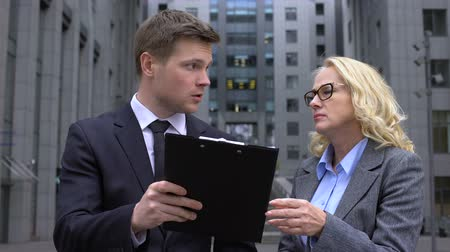 criticize : Male company worker discussing contract details with mature female colleague Stock Footage