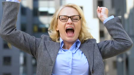 suceder : Extremely happy female employee gesturing Yes, celebrating salary increase