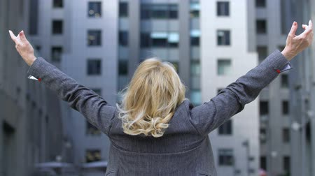eufória : Business lady raising arms, confident in goal achievement, success motivation Stock mozgókép
