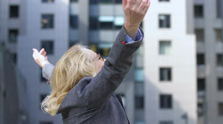 eufória : Joyous mature lady raising arms, celebrating success, winner and leader for life