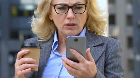 koffie verkeerd : Elderly businesswoman upset with message on smartphone, communication app