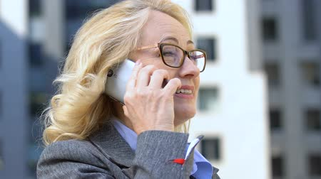 поставщик : Cheerful female official talking on cell phone, efficient mobile negotiations