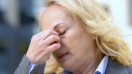 tiredness : Old woman office worker rubbing eyes from tiredness, blurred vision, closeup Stock Footage