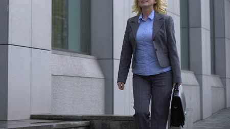 werk zoeken : Cheerful business lady with briefcase walking near office building, loving job