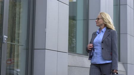 rekrutacja : Happy business lady walking near office building, satisfied with loving job