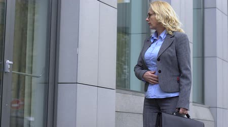 licenziamento : Mature woman watching reflection in window, feels insecure before job interview