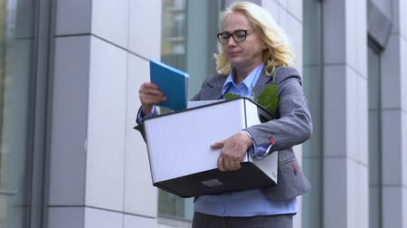 занятость : Woman angrily throws things out of box, upset by unfair dismissal, job cuts