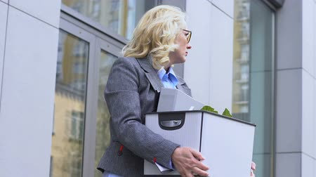 jobless : Beautiful old woman holding cardboard box, upset by dismissal, resignation Stock Footage