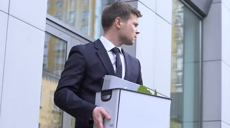 licenziamento : Young man carrying box with personal belongings, depressed about dismissal