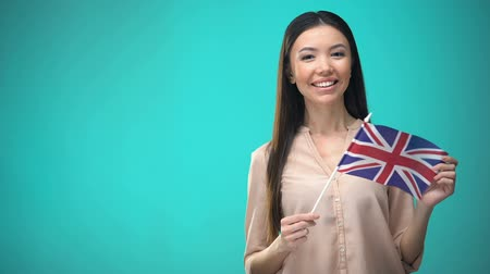financiamento : Smiling woman holding Great Britain flag, ready to learn foreign language Vídeos