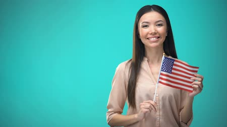 finansman : Cheerful girl holding USA flag, ready to learn foreign language, English school Stok Video