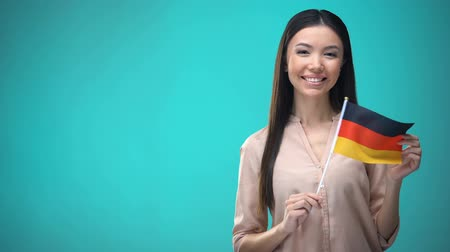 financiamento : Smiling lady holding Germany flag ready to learn foreign language, German school Vídeos