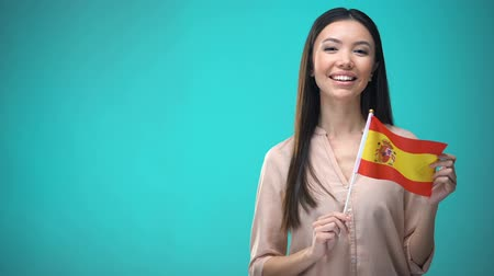 financiering : Cheerful girl holding Spain flag ready to learn foreign language, Spanish school Stockvideo