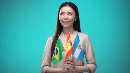 brezilya : Curious woman holding Brazil, Spain and Argentina flags, learning language