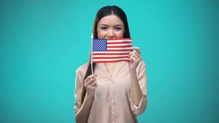zahraniční : Woman covering face with USA flag, learning language, education and travel Dostupné videozáznamy
