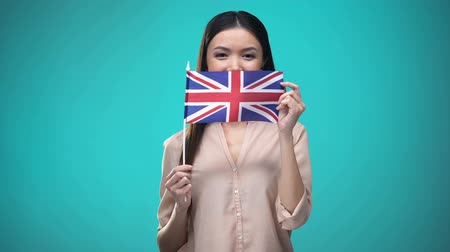 zahraniční : Girl covering face with British flag, learning language, education and travel