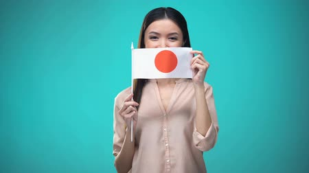 financiamento : Woman covering face with Japan flag, learning language, education and travel
