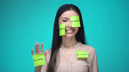 lichaamsdelen : Female student learning Italian, covered with body parts sticky notes, education