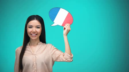 gramatika : Smiling girl holding French flag speech bubble, learning language, travel ideas