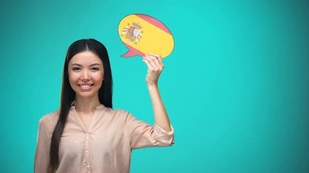 middelbare school : Smiling girl holding Spanish flag speech bubble, learning language, travel ideas
