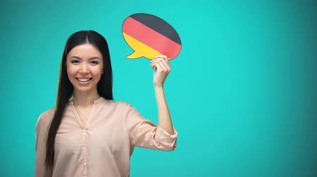 middelbare school : Smiling girl holding German flag speech bubble, learning language, travel ideas Stockvideo
