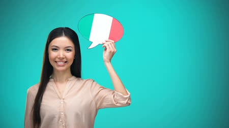 gramatika : Smiling girl holding Italian flag speech bubble, learning language, travel ideas Dostupné videozáznamy