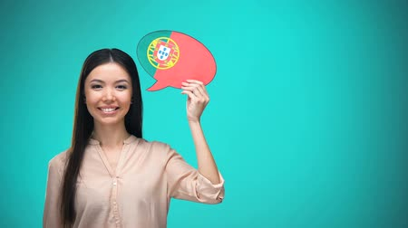 gramatika : Smiling girl holding Portuguese flag speech bubble learning language travel idea