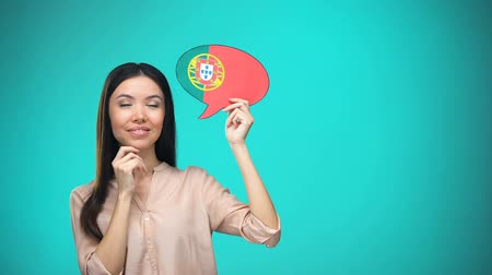 egyetem : Curious woman holding Portuguese flag sign, learning language, education abroad
