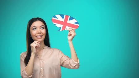 estrangeiro : Curious woman holding British flag sign, learning language, education abroad