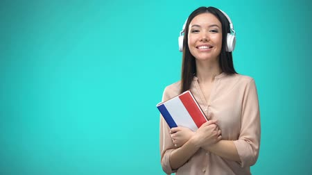 aksan : Girl listening French audio lessons in headset, book in hands, translations