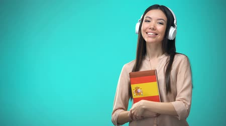 aksan : Girl listening Spanish audio lessons in headset, book in hands, translations
