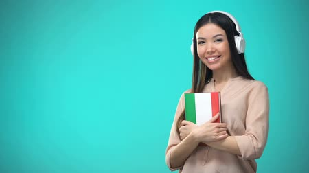 aksan : Girl listening Italian audio lessons in headset, book in hands, translations