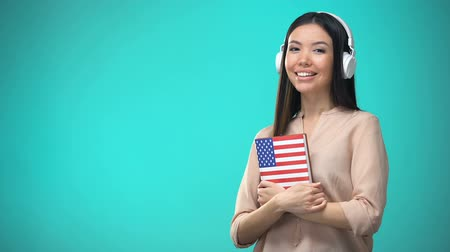 accent : Girl student listening American English audio lessons in headset, book in hands
