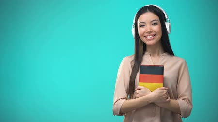 辞書 : Girl listening German audio lessons in headset, book in hands, translations
