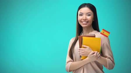 consulate : Cheerful woman holding Spanish flag book, education abroad, learning language Stock Footage