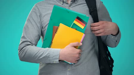 písanka : Male student holding notebooks with German flag, international education program