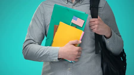 písanka : Student holding notebooks with USA flag, international education program